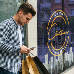 Man checking phone holding shopping bags standing in front of window graphics